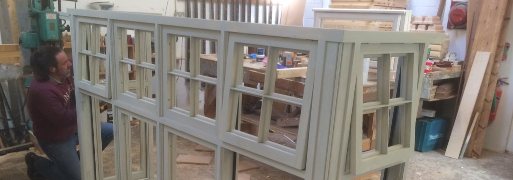 Staff member sanding wooden window frame